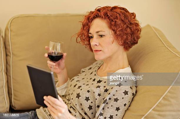 Using electronic tablet with a glass of wine