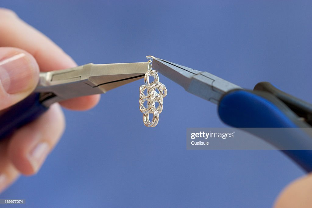 Using Flat Nose Pliers To Make Silver Wire Jewelry Stock Photo ...