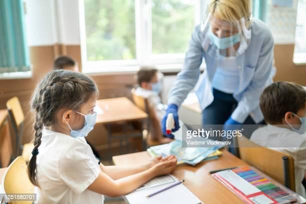 covid-19. using hand sanitizer in the classroom - educazione foto e immagini stock