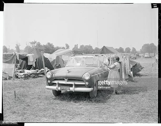 Using her care as a support for line Mrs MJ Dealey of Bellflower CA checks to see if her days laundry has dried at Jehovah's Witnesses tent city New...