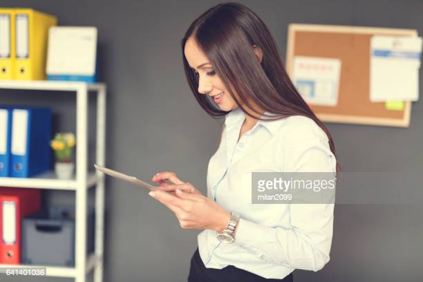 using her tablet at the office - milan2099 stock photos and pictures