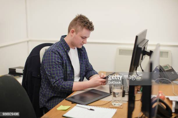Using his Phone at his Desk