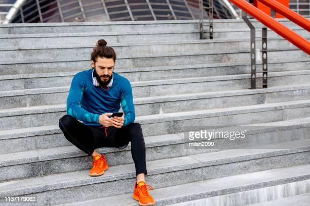 uso del suo smartphone dopo l'esecuzione - abbigliamento sportivo foto e immagini stock