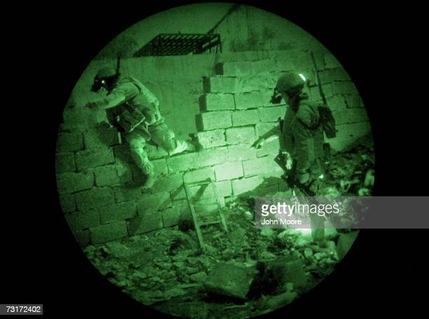 Using infrared lights only visible with night vision goggles, U.S. Marines conduct a search operation for insurgents January 28, 2007 in Ramadi in...