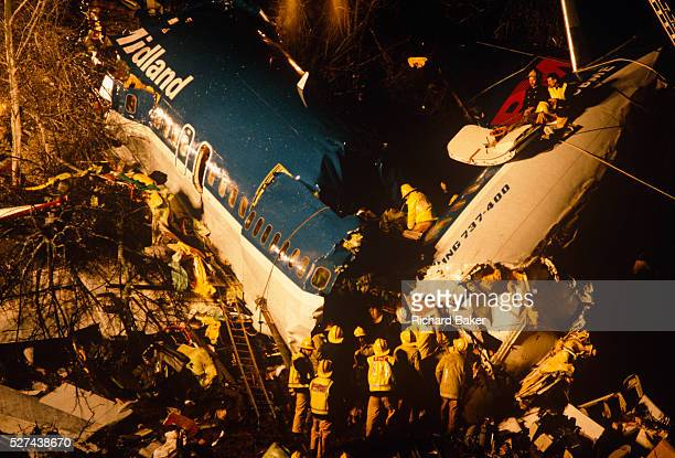 Using ladders and ropes during a rescue operation Fire Brigade crews enter the floodlit broken air frame of a British Midland Airways Boeing 737400...