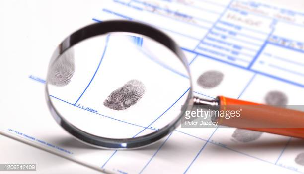 using magnifying glass to look at finger and thumb prints - malfaiteur photos et images de collection