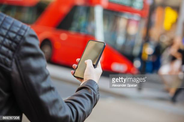 Using mobile phone on the street with red double decker bus in background, close up