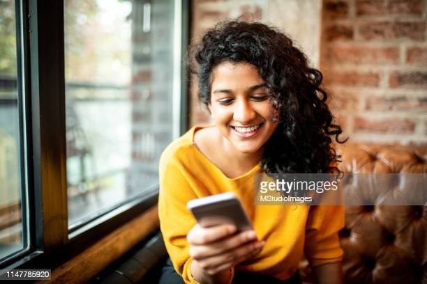 using mobile phone. - indian culture stock pictures, royalty-free photos & images