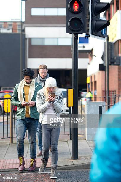 using mobile telephone while crossing a road - road signal stock pictures, royalty-free photos & images