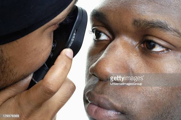 Using ophthalmoscope to examine young mans eye