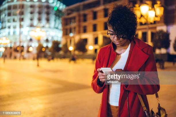 using phone downtown - warm clothing stock pictures, royalty-free photos & images