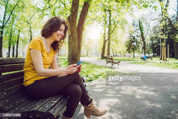 using phone in a park - phone message stock pictures, royalty-free photos & images