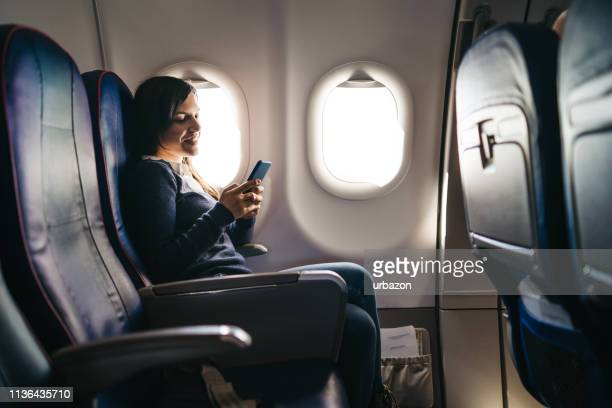 using phone on an airplane ride - seat stock pictures, royalty-free photos & images
