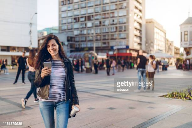 using phone on town square - phone message stock pictures, royalty-free photos & images