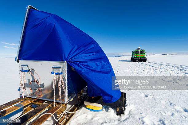 Using radar a scientist sends radio waves to the base of the ice and measures the return time to measure the thickness