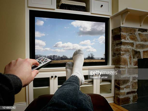 using remote with feet in front of flat screen - feet up stock pictures, royalty-free photos & images
