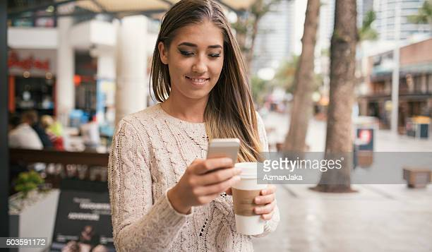 Using smart phone while drinking coffee