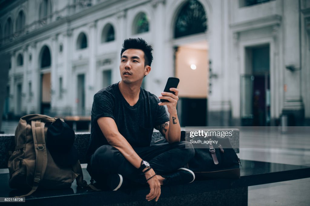 Using smart phone while waiting for my train : Stock Photo