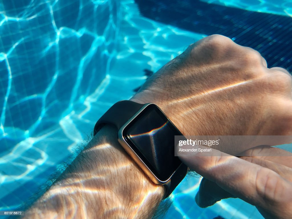 Using smart watch in the swimming pool underwater : Stock Photo
