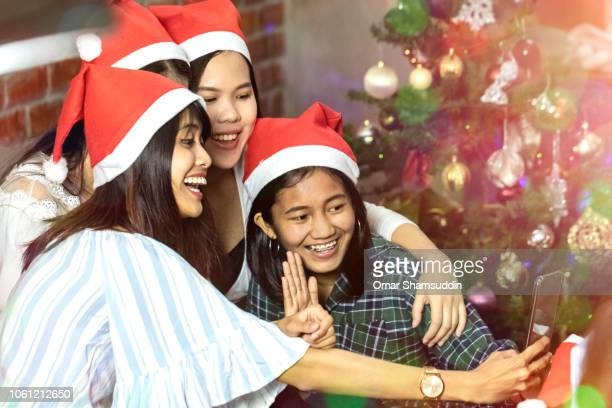 Using smartphone during Christmas celebration with friends in Malaysia