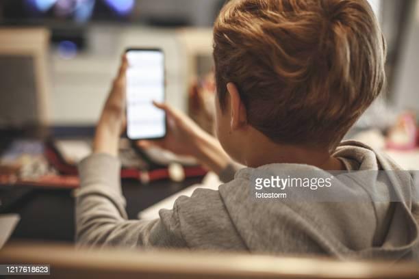 verwenden des smartphones während der quarantänezeiten zum abschließen von homeworks - digital native stock-fotos und bilder
