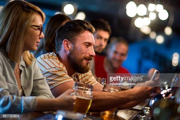 Mit Smartphone in einem pub