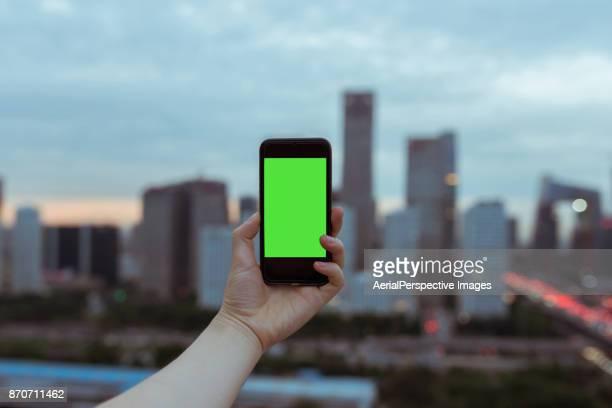 Using Smartphone Standing on Skyscraper Roof