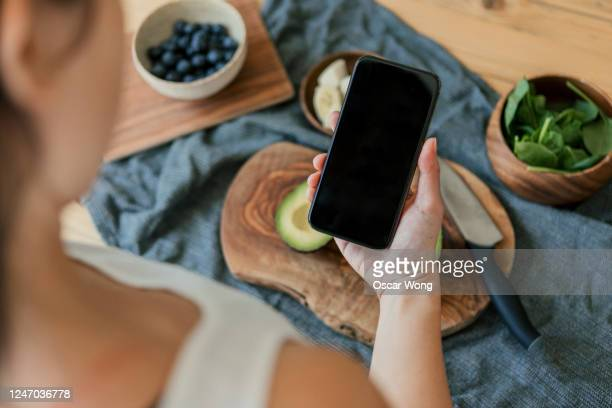 using smartphone while preparing vegan food on a wooden worktop - telephone stock pictures, royalty-free photos & images