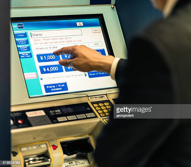 Using teller machine to re-charge IC transport card in Tokyo
