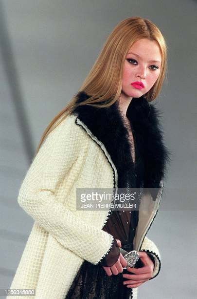 USJapanese model Devon Aoki presents a white coat with fur lapels over a black gown for Chanel during the AutumnWinter 2000/2001 readytowear...