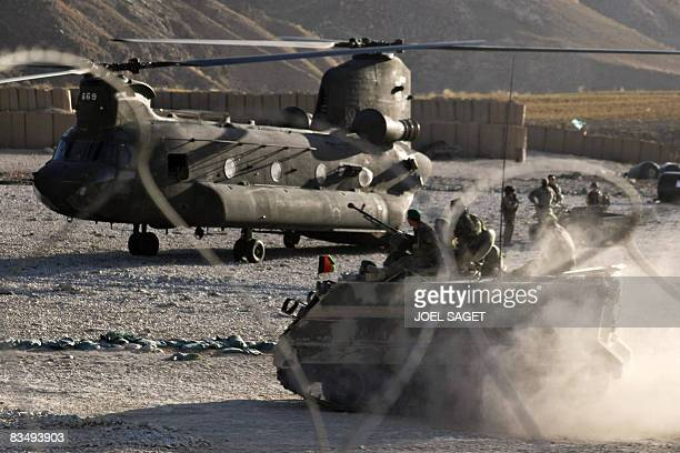 A USmade M113 armoured personnel carrier from the Afghan National Army drives past a US Army CH47 Chinook heavylift helicopter at Forward Operating...