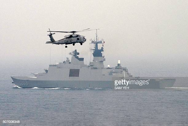 A USmade S70C helicopter files over a Frenchmade Lafayette frigate during a drill at sea near the naval port in Kaohsiung in southern Taiwan on...