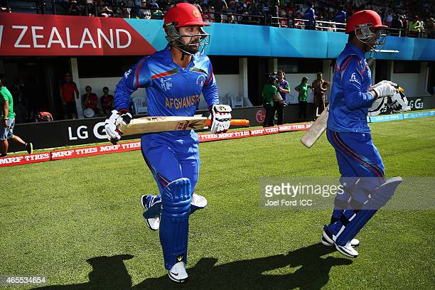 Usman Ghani and Javed Ahmadi of Afghanistan walk onto the field during the 2015 ICC Cricket World Cup match between New Zealand and Afghanistan at...