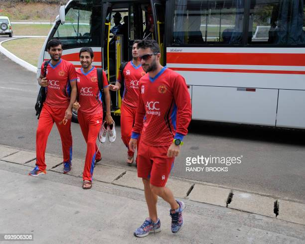 Usman Ghani and Karim Janat of Afghanistan disembark their bus to take part in a training session at Darren Sammy National Cricket Stadium on June 08...