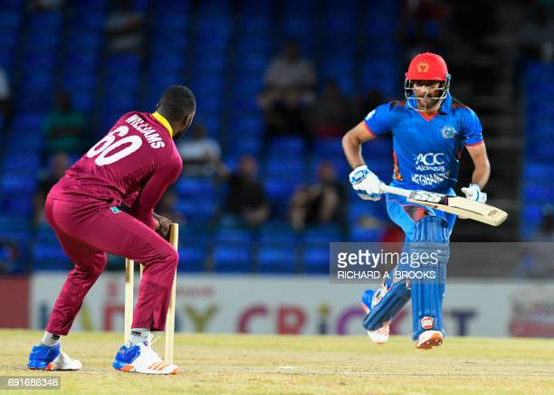 Usman Ghani of Afghanistan run out by Kesrick Williams of West Indies during the 1st T20i match between West Indies and Afghanistan at Warner Park...