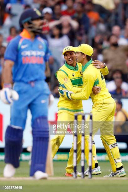 Usman Khawaja and Alex Carey of Australia celebrate the wicket of Virat Kohli of India during game three of the One Day International series between...