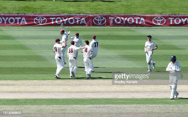 Usman Khawaja and Mitch Swepson of Queensland celebrates taking the wicket of Nathan Lyon of New South Wales during day four of the Sheffield Shield...