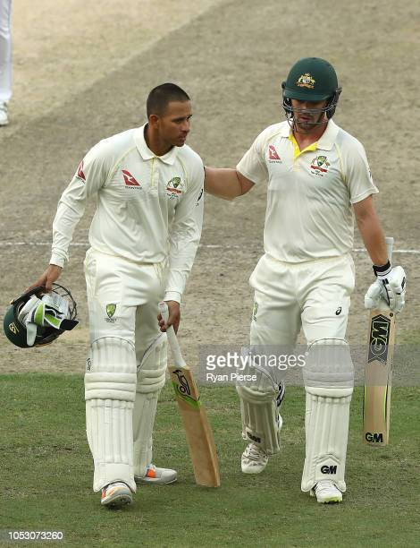 Usman Khawaja of Australia and Travis Head of Australia walk from the ground at stumps during day four of the First Test match in the series between...