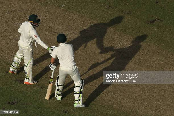Usman Khawaja of Australia shakes hands with Steve Smith after scoring his half century during day two of the Third Test match during the 2017/18...