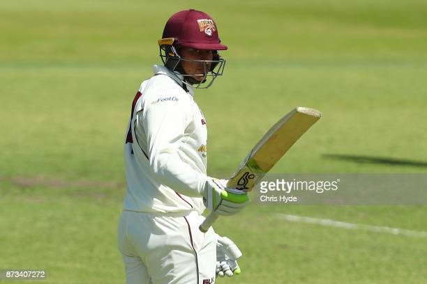 Usman Khawaja of Queensland celebrates his half century during day one of the Sheffield Shield match between Queensland and New South Wales at Allan...