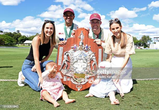 Usman Khawaja of Queensland poses for a photo as he celebrates victory with wife Rachel Khawaja and daughter Aisha Khawaja and Jimmy Peirson of...