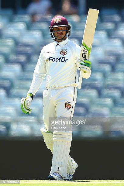 Usman Khawaja of Queensland raises his bat to celebrate his 150 during day two of the Sheffield Shield match between Western Australia and Queensland...
