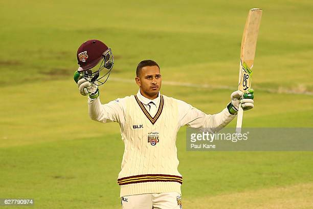 Usman Khawaja of Queensland raises his bat to celebrate his century during day one of the Sheffield Shield match between Western Australia and...