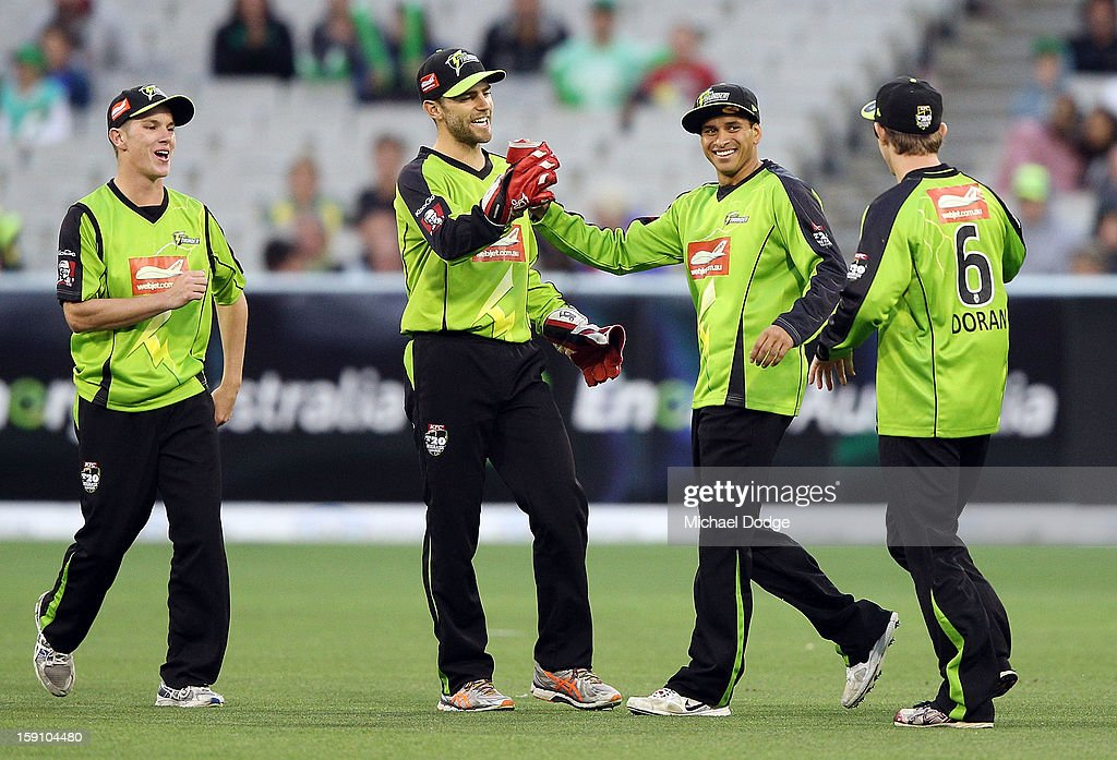 Usman Khawaja (2nd R) of the Sydney Thunder celebrates his catch to dismiss Rob Quiney of the Melbourne Stars with teamate Ryan Carters during the Big Bash League match between the Melbourne Stars and the Sydney Thunder at Melbourne Cricket Ground on January 8, 2013 in Melbourne, Australia.
