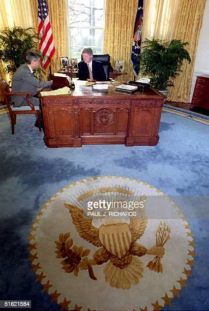 President Bill Clinton sits behind the same desk used by Presidents John F Kennedy and Ronald Reagan as he meets with Bob Rubin chairman of the...