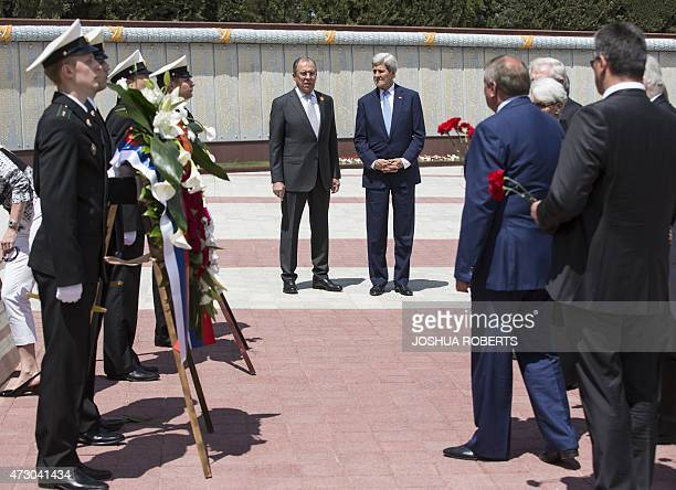 USSecretary of State John Kerry and Russian Foreign Minister Sergey Lavrov watch as members of the US and Russian delegations place red flowers at...