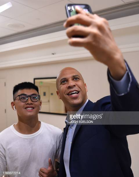 USSenator and Presidential candidate Cory Booker takes a selfie with a fan before the start of the Democratic National Committee's summer meeting in...
