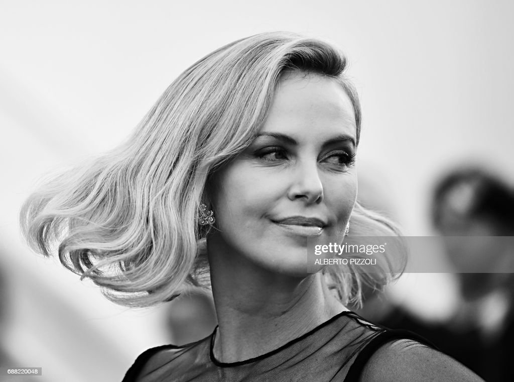 US-South African actress Charlize Theron poses as she arrives on May 23, 2017 for the '70th Anniversary' ceremony of the Cannes Film Festival in Cannes, southern France. / AFP PHOTO / Alberto PIZZOLI