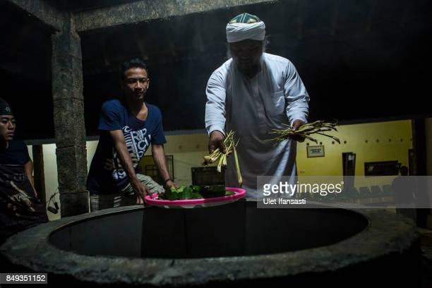 Ustad Ahmad Ischsan Maulana the head of Nurul Ichsan Al Islami traditional rehabilitation centre prepares a hot water herbal bath for recovering...