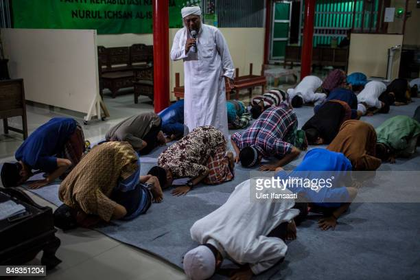 Ustad Ahmad Ischsan Maulana the head of Nurul Ichsan Al Islami traditional rehabilitation centre prays with recovering drug addicts during a prayer...